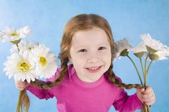 Image of lovely girl with white flowers in both hands looking at camera and smil Stock Photos