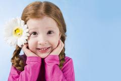 Portrait of charming girl with flower in hair touching her face over blue backgr Stock Photos