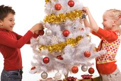 Photo of happy girl and boy decorating new year tree with toy balls Stock Photos