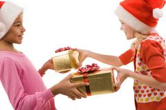 Portrait of happy friends exchanging christmas gifts on eve Stock Photos