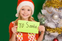 happy girl holding letter with note 'to santa' with decorated firtree near by - stock photo