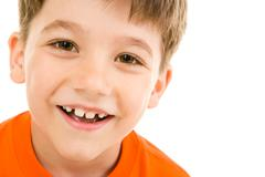 Face of smiling boy with brown eyes on a white background Stock Photos