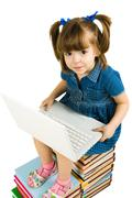 photo of schoolgirl sitting on books and learning how to use laptop - stock photo