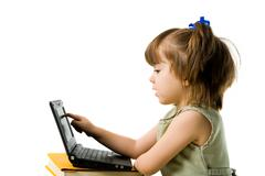 profile view of serious preschooler pointing at laptop display - stock photo