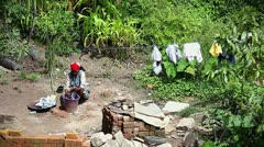 An old woman washes clothes in a dirty slum in Madagascar. Stock Footage