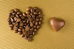 image of two shapes of heart: made up of grained coffee and chocolate toffee - stock photo