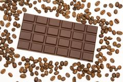 Wallpaper of chocolate bar surrounded by coffee beans over white background Stock Photos