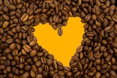 Backdrop of yellow heart shape inside coffee grains Stock Photos