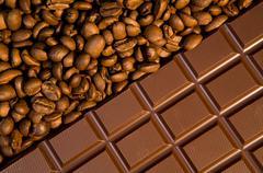 Macro image of dark chocolate bar with heap of coffee grains near by Stock Photos