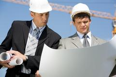 Portrait of two architects looking at project on construction site Stock Photos