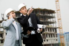 Photo of serious employee pointing at something with calling foreman standing ne Kuvituskuvat