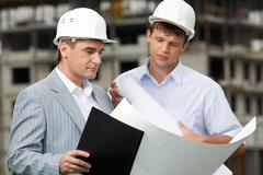 portrait of confident colleagues looking at new construction plan and brainstorm - stock photo