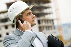 portrait of serious architect calling on the telephone on the background of buil - stock photo