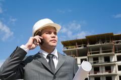 Portrait of confident foreman calling by the phone and holding document Stock Photos