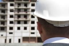 Close-up of builder head wearing white helmet with building under construction a Stock Photos