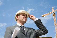 Portrait of confident foreman in helmet touching it by hand with blue sky above Stock Photos