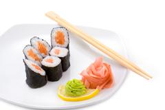 image of sake hosomaki sushi with pickled ginger and wasabi on a plate - stock photo