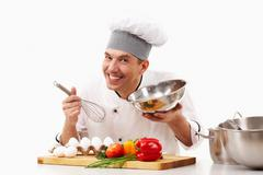 Portrait of handsome man in cook uniform smiling at camera during work Stock Photos