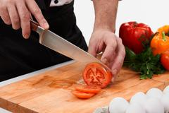 Image of male hand with knife cutting tomatoes on wooden chopping board Stock Photos