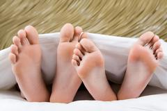 image of two pairs of bare feet of man and woman lying under blanket - stock photo