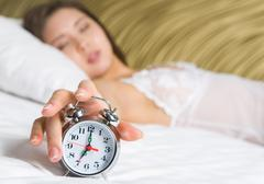 image of female hand on top of alarm clock after awakening in the morning - stock photo