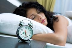 Image of alarm clock on background of sleeping female Stock Photos