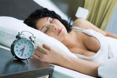 image of alarm clock on background of sleeping female in the morning - stock photo