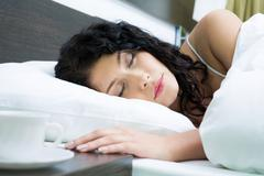 Photo of pretty woman sleeping peacefully in white linens Stock Photos