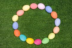 Stock Photo of background of circle made up of colored easter eggs on green grass