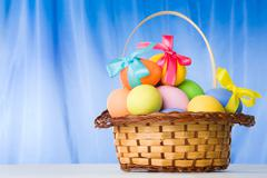 Image of easter theme with basket full of colorful eggs over blue background Stock Photos