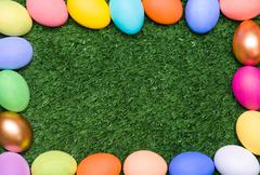 background composed as colorful egg framing a piece of grassland - stock photo