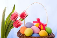 Tulip bouquet with basket of easter eggs near by over blue background Stock Photos