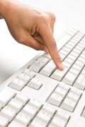 close-up of female forefinger pressing enter button of computer keyboard - stock photo