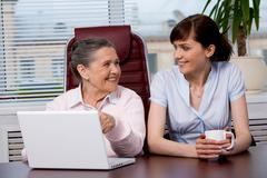 Portrait of elderly woman consulting her pretty granddaughter what to type Stock Photos