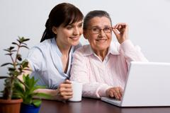 portrait of young girl looking at laptop monitor with her cheerful granny smilin - stock photo