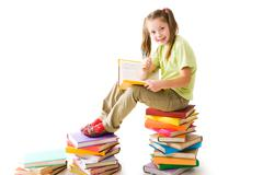 Portrait of cute schoolgirl sitting on top of heap with open book and looking at Stock Photos