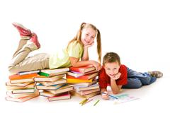 smart girl lying on top of book piles with cute schoolboy drawing near by - stock photo