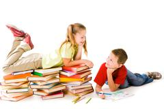 smart girl lying on top of book piles and talking to cute schoolboy drawing near - stock photo