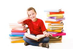 Image of schoolboy sitting between two heaps of books and reading one of them Stock Photos