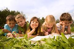Portrait of cute kids reading books and drawing in natural environment together Stock Photos