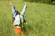 Stock Photo of portrait of cute girl standing in green grass with her arms raised