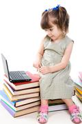 image of curious preschooler sitting on books and looking at laptop display - stock photo