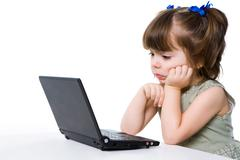 Portrait of elementary school girl looking at laptop screen with thoughtful expr Stock Photos