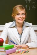 portrait of young teacher checking up copybook with books near by and looking at - stock photo