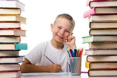 portrait of cute youngster sitting among stacks of literature and smiling at cam - stock photo