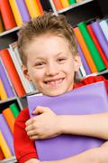 Portrait of handsome boy with violet book in library looking at camera Stock Photos