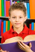 Portrait of smart boy with open book looking at camera in library Stock Photos