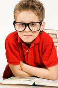 Stock Photo of portrait of clever boy wearing eyeglasses with open book in front looking at cam