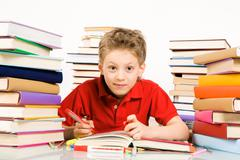 Portrait of cute youngster sitting among stacks of literature with open book in Stock Photos