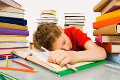 Image of tired schoolboy sleeping on pages of textbook with pink pencil in hand Stock Photos